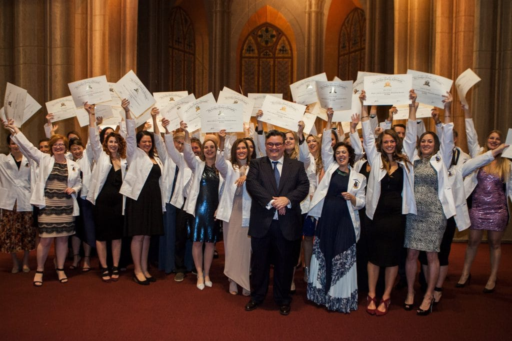 Principal Robert Johnston stands with recent graduates of the Canadian Academy of Osteopathy
