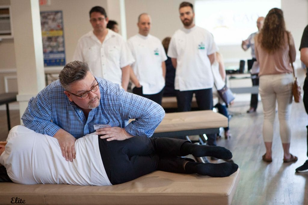 Principal Robert Johnston using osteopathic techniques on a student of the CAO, who is lying on a clinical table