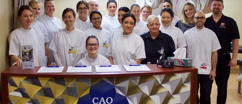 Students of the CAO standing at the student clinic celebrating 30,000 free treatments